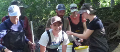 Volunteers with a net doing river monitoring of fish