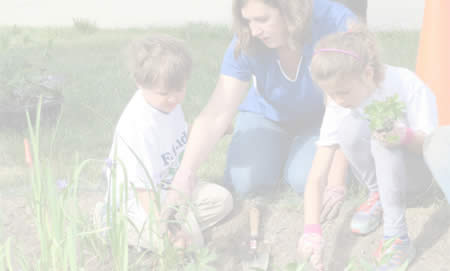 Photo of mother showing her two children how to plant seeds
