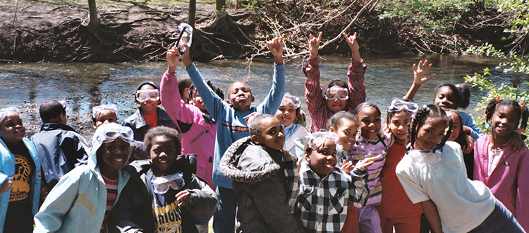 Children with arms raised and happy, at the Rouge River