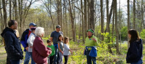 Group of people listening to a volunteer in the woods along the Rouge River