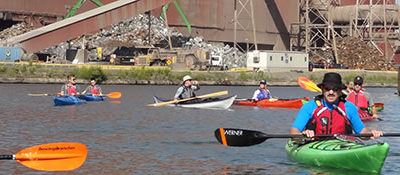 Many kayakers enjoying the Rouge River Water Trail in front of a manufacturing facilty
