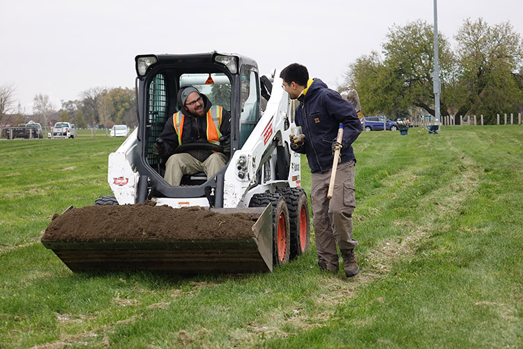 Greening of Detroit Community Forester Drew Decker brings soil for the tree planting in Patton Park, view facing southwest