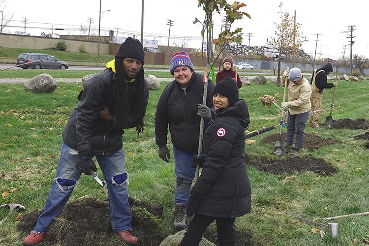 Greening of Detroit employee Ayatallah el Amin and citizen foresters Ellen Beeman and Mollika Bierna plant a tree in Patton Park, view facing north towards Dix Avenue