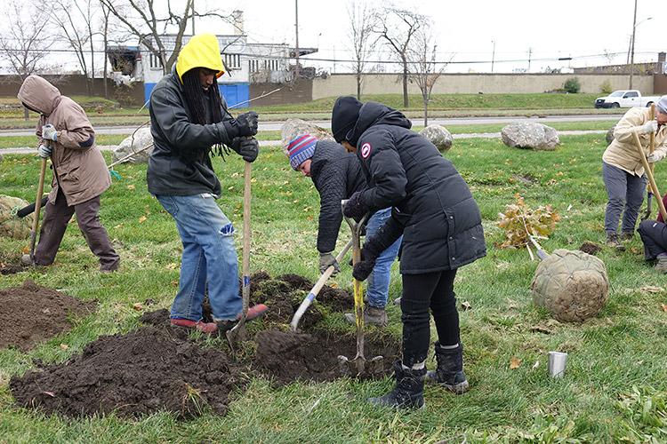 Greening of Detroit employee Ayatallah el Amin (left, yellow hood) digs a tree hole with citizen foresters Ellen Beeman and Mollika Biernat, view facing northwest towards Dix Avenue