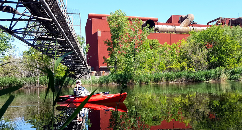 Man kayaking on the Rouge River in front of an industrial plant and under a bridge