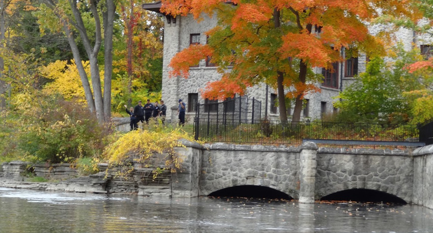 Beautiful fall color of trees and people waving from a home along the Rouge River, river view