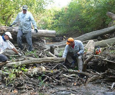 Three men working to remove a logjam