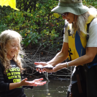 FOTR staff handing turtles to a young volunteer