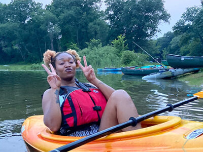 Browns & Blacks In Kayaks-2021 featured image woman giving the double-victory pose
