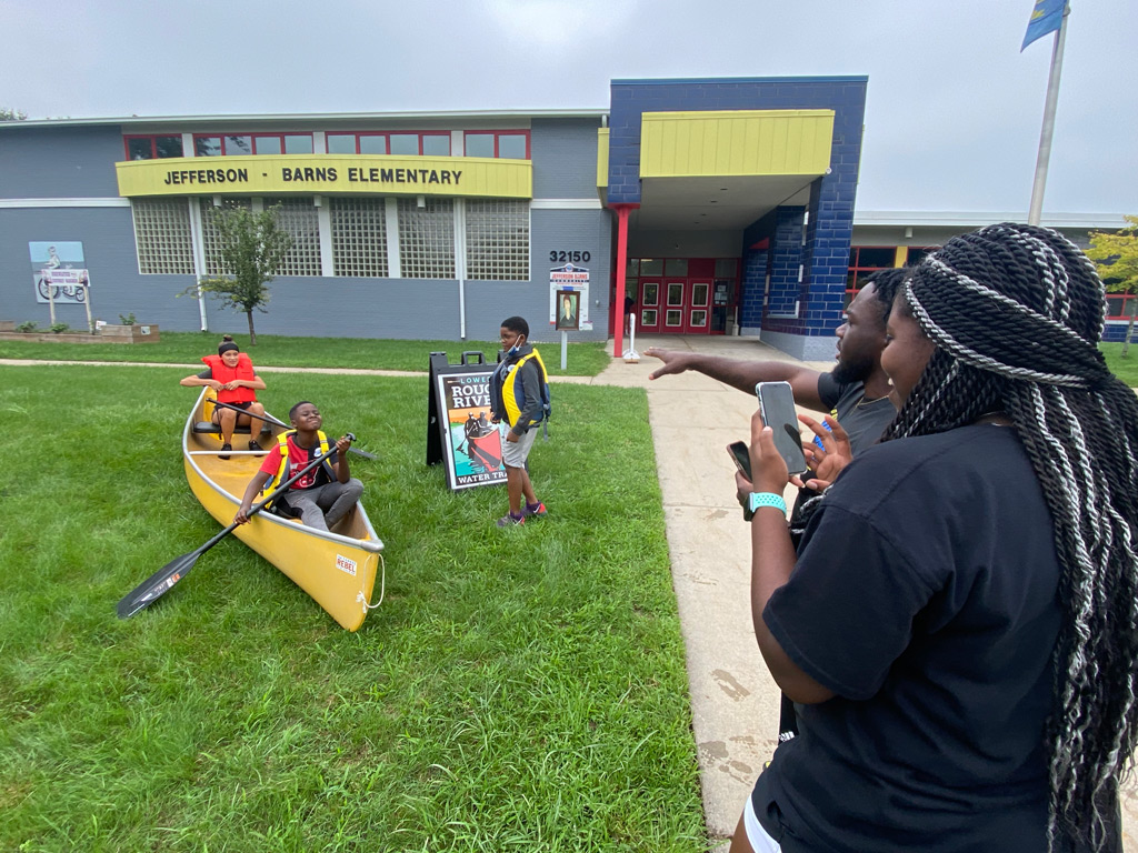 Jeffersen-Barnes Dry Dock Pop Up parents taking photo of two students in the canoe with life jackets and paddles