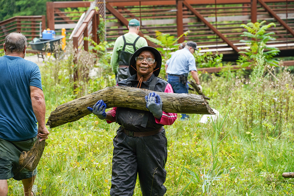 Log Jam Day 072421 woman carrying a mid-sized log